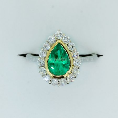 Bezel Set Emerald in a Diamond Halo Ring in 18K Gold